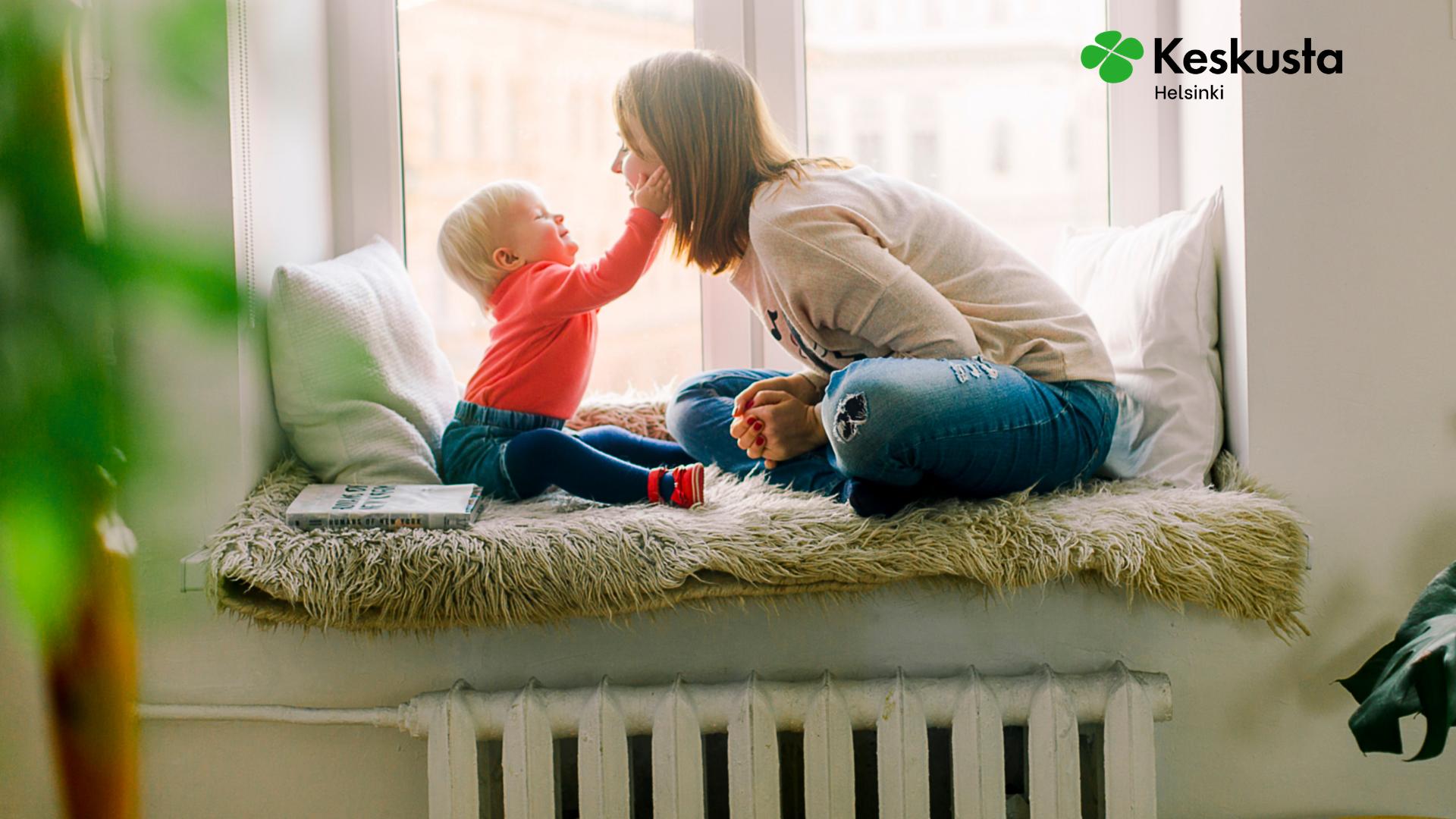 Pieni lapsi ja äiti istuvat ikkunalaudalla. Perhevapaauudistus on voitto perheille