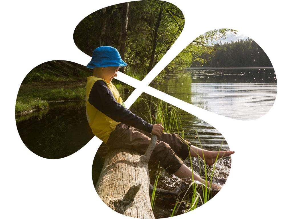 Poika istuu puun rungolla veden äärellä
