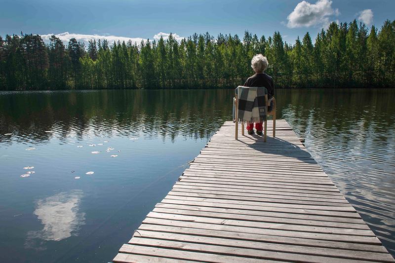Ikäihminen laiturinnokassa tuolissa, järvi ja metsä maisemaa