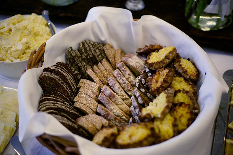 Tarjoilupöytä korissa ruis- ja vehnäleipää sekä karjalanpiirakoita