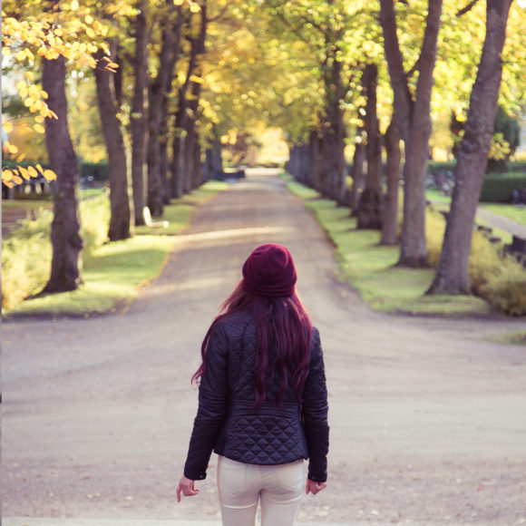 nainen etualalla, kävelee kohti puistotietä. Sen reunoilla syksyisen keltaiset puut.