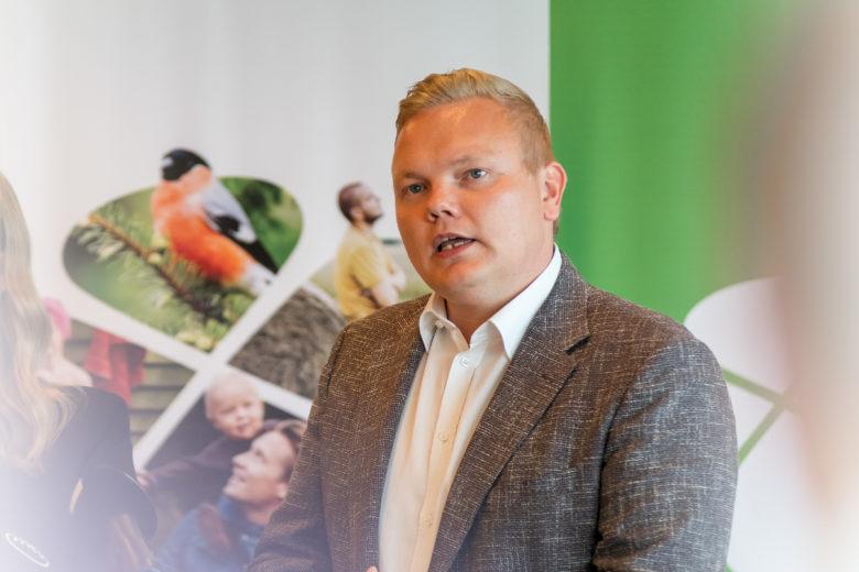 Antti Kurvinen tiedoitustilaisuudessa. Taustalla keskustan uusi logo ja kuvilla täytetty apila.