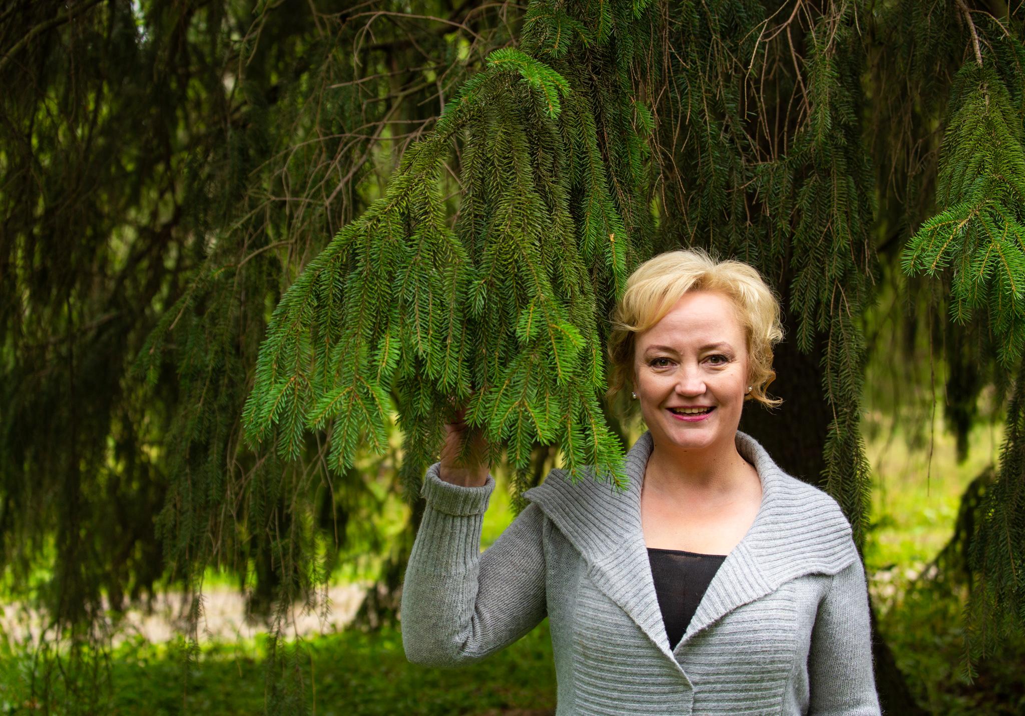 europarlamentaarikko Elsi Katainen pitelee suurta kuusen oksaa suomalaisessa metsässä