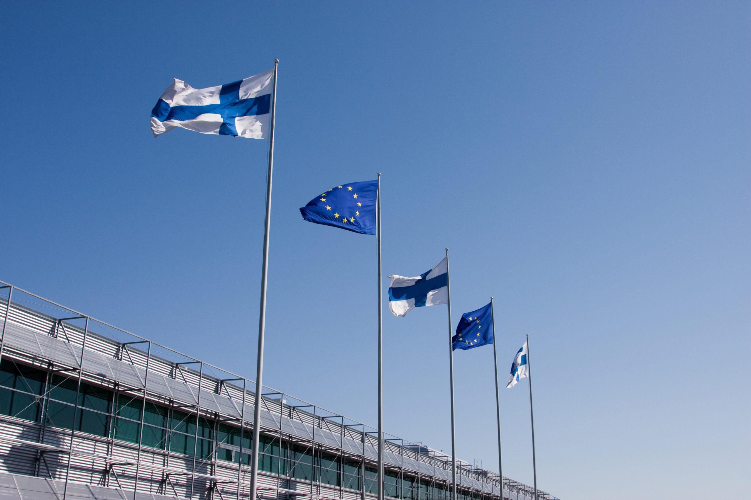 lippuja lipputangoissa, kolme Suomen lippua ja kaksi EU:n lippua