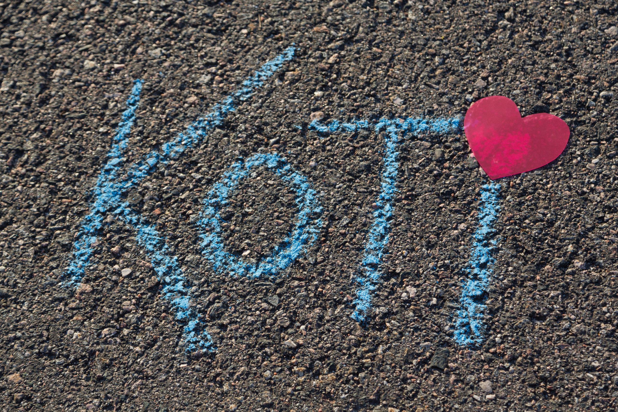 KOTI-teksti sinisellä liidulla piirrettynä asvaltissa, missä ii:n pisteenä sydän