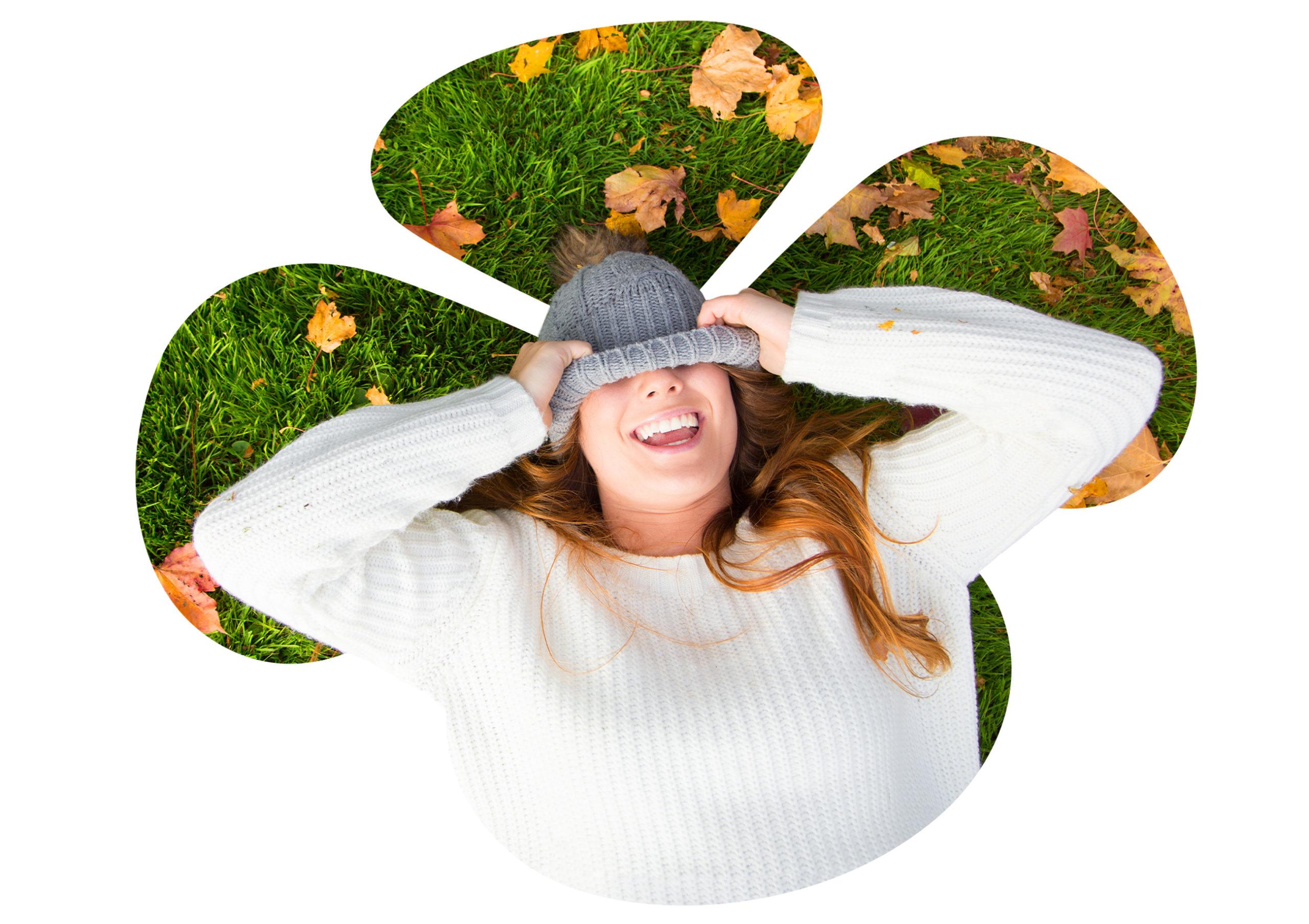 ihminen hattu silmillään maassa makaamassa, syksyisiä lehtiä ympärillä.