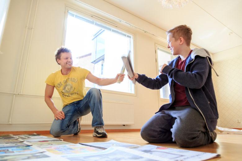 Iloiset asunnon remontoijat kippistelevät pensseleillä