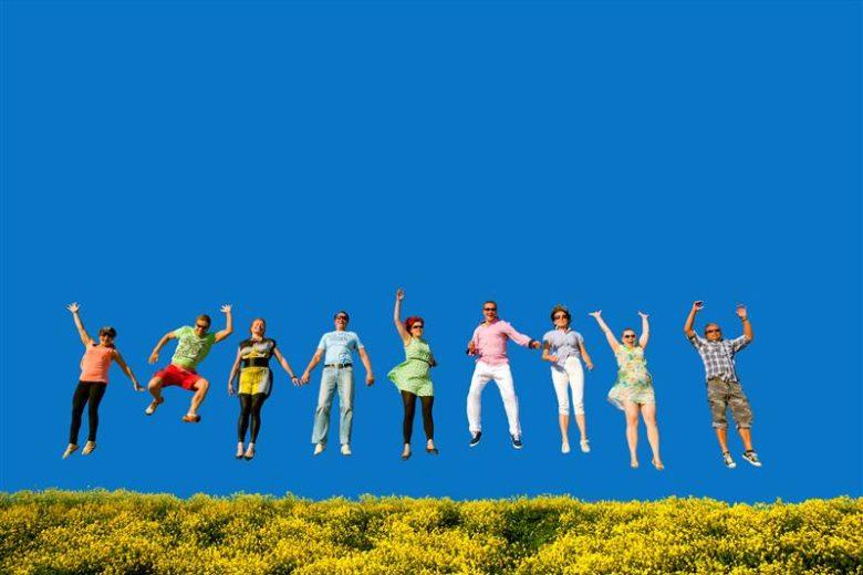 joukko ihmisiä rivissä, hyppäävät ilmaan. Aurinkoinen päivä ja kirkas taivas.