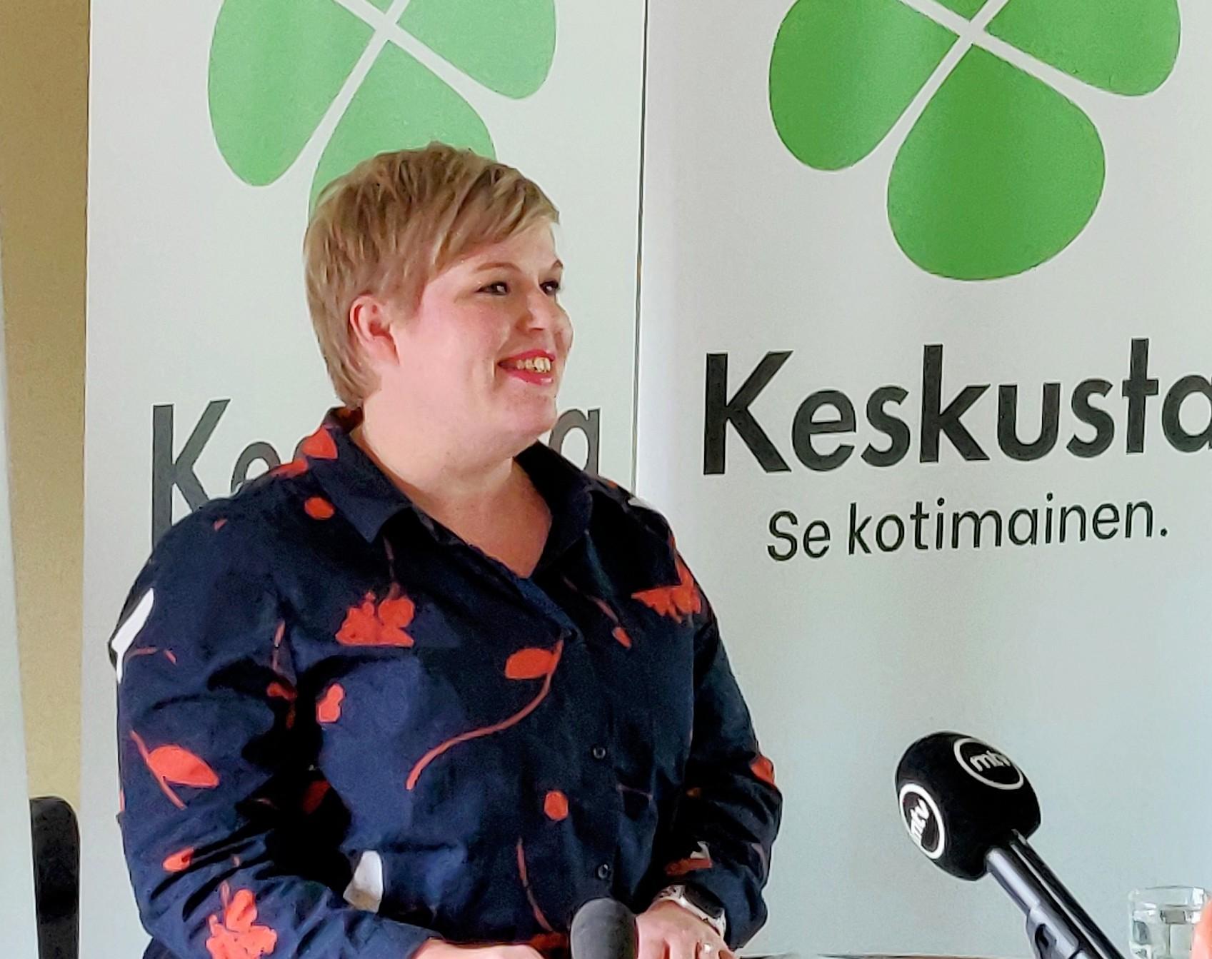 Annika Saarikko pitämässä puhetta, taustalla Keskustan logo ja slogan